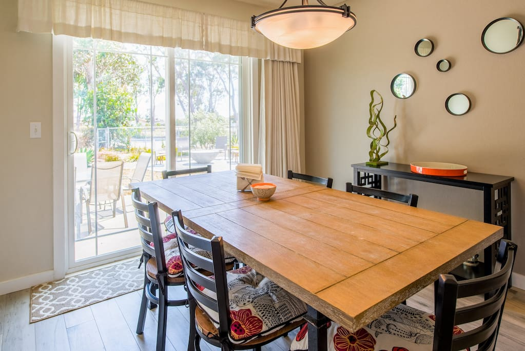 A wood dining table seats six with views of Morro Rock through the patio door