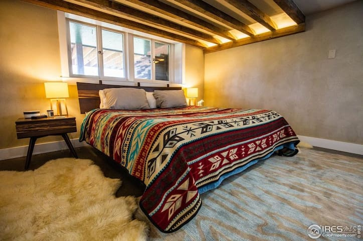 The master bedroom as a luxurious king-sized bed and exposed wood beams overhead.