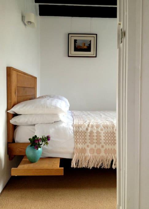 Bespoke oak bed and original ceiling beams.