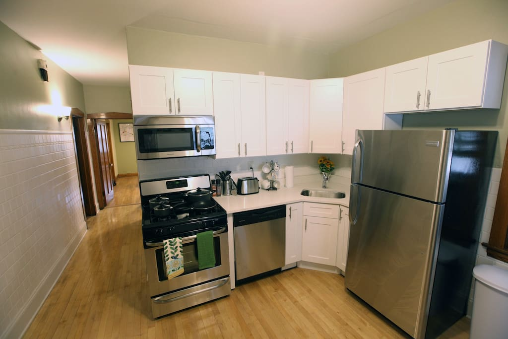 Well appointed brand new kitchen with stainless steel appliances, quartz countertops, and everything you need to feel right at home including plates, glasses, bowls, flatware, wine glasses, coffee mugs, & cooking utensils