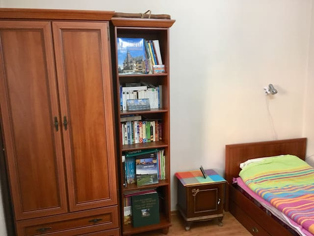 Cupboard, bookshelf, bedside table and bed with lamp