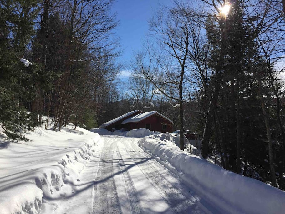 Winter view of house from road. Notice Killington ski trails in background.