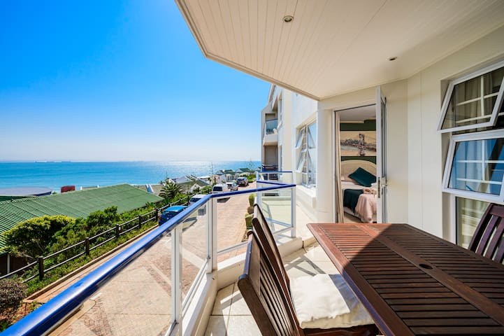 Balcony view of the beach, parking lot and open door leading to the main bedroom to the right.