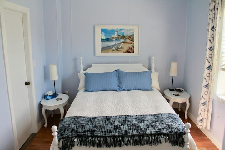 Main bedroom and comfortable queen bed, side tables, bedside reading lamps, and clock radio.