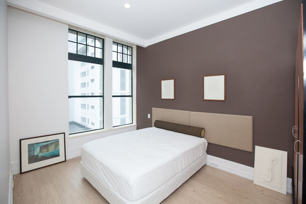 A comfortable queen bed with large window overlooking Hobson Street.