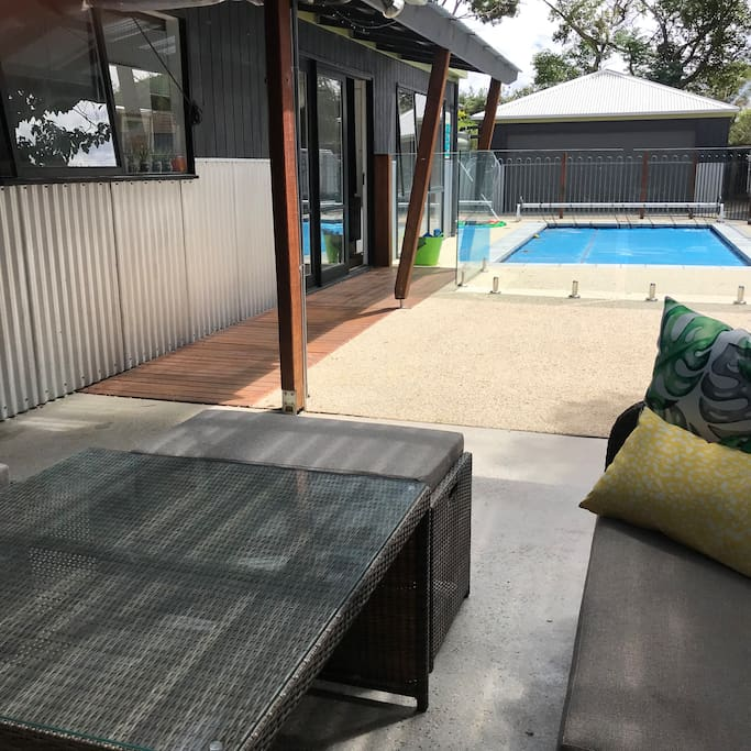 Outdoor covered BBQ area with sofa style seating, small bar fridge, and Weber overlooking the pool