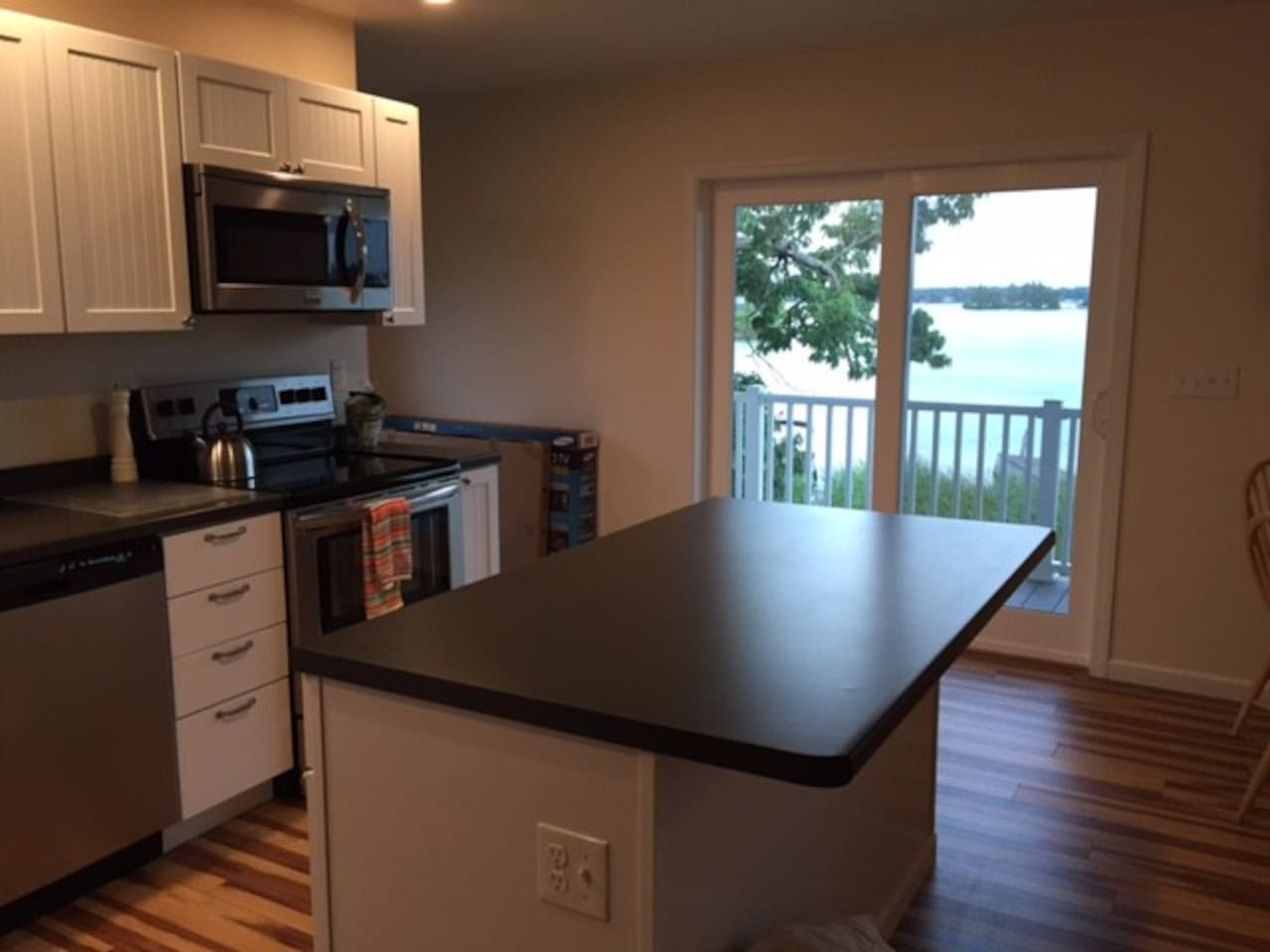 Open Kitchen to Balcony and Living Room. Overlooks Fire Pit and Dock