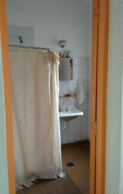 El baño es pequeño: ducha, lavamanos e inodoro. Dos puertas de acceso.