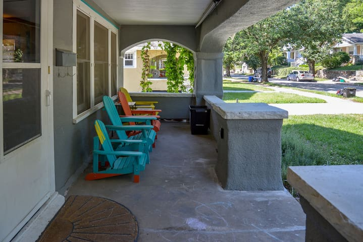 Spacious front porch with Adirondack chairs and sun shade .