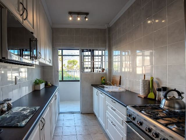 Galley kitchen with all the necessities including microwave, toaster, gas stove, espresso maker plus many more