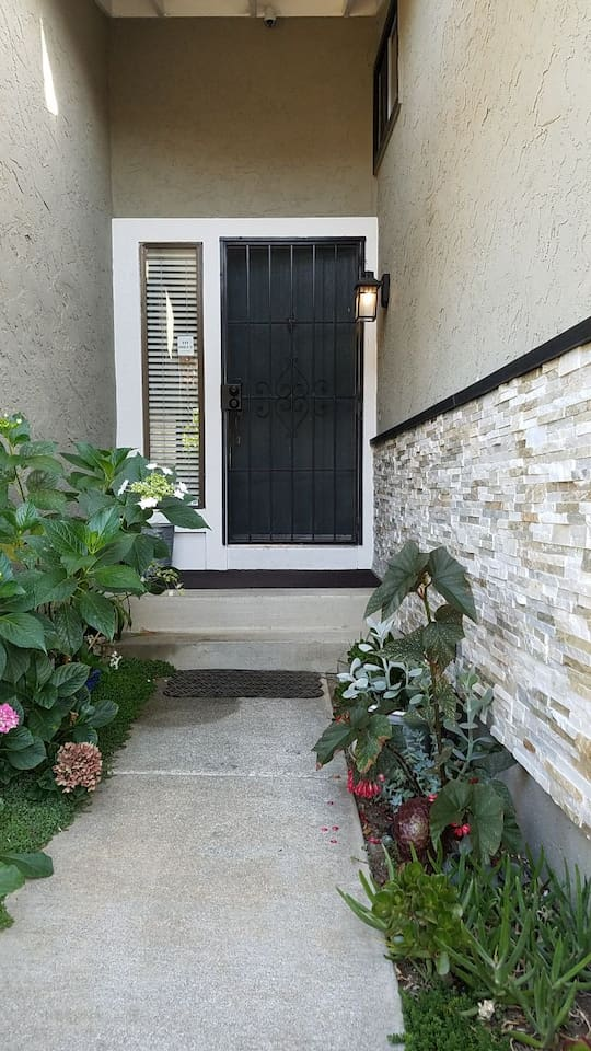 Front door with a key code lock and succulent and flower garden