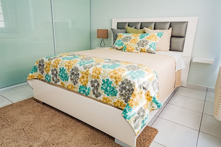 This is guest bedroom one equipped with a queen size mattress covered by Peacock Alley linens both mattress and linens are of the highest quality closet is very large fits a full suitcase this room has bath towels and beach towels for two people