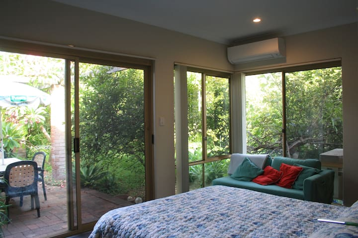Bedroom with new air conditioner, queen bed, chaise lounge, outdoor setting and peaceful green garden.