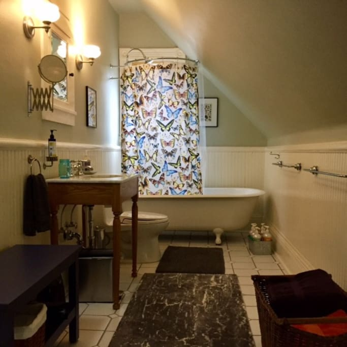 Private bathroom with claw foot tub and natural shampoos and soaps.