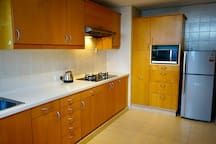 Kitchen with stove, fridge and microwave oven