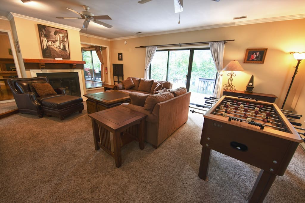 Living room with fireplace, comfy couches and foosball table