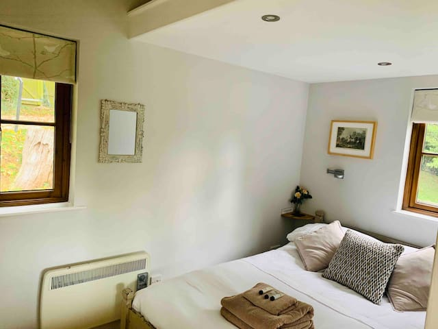 Cosy and snug double bedroom with double aspect, stable door between bedroom and living area, full height wardrobes and a storage area above bed.