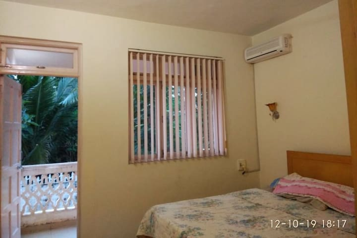 Bedroom with air conditioner and outside balcony