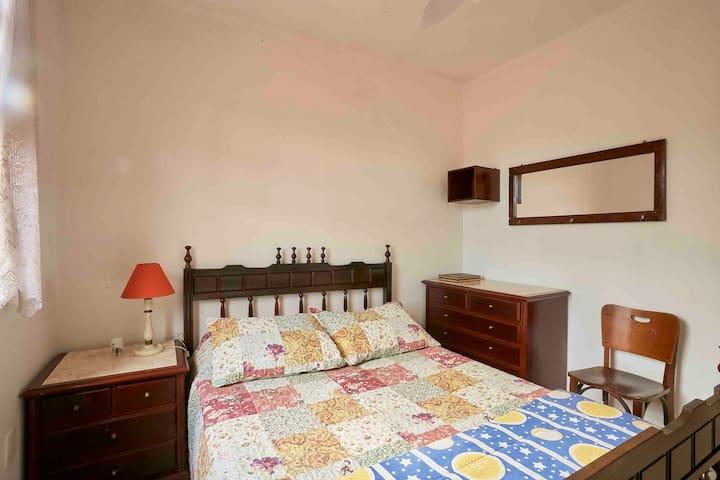 Quarto no piso superior com vista para o jardim, ventilador de teto, cama de casal, contendo além das roupas de cama, toalhas, shampoo e sabonete.