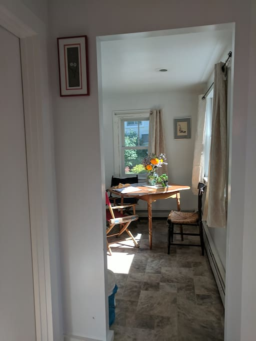 View of kitchen table from entry  looking to the right (bathroom door on left, main entry door on far right).