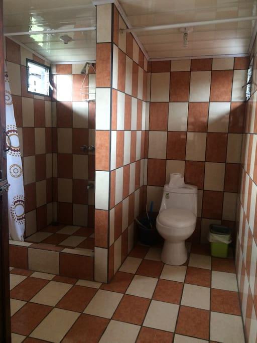 Vista interna del cuarto de baño con agua caliente y lavado incorporado