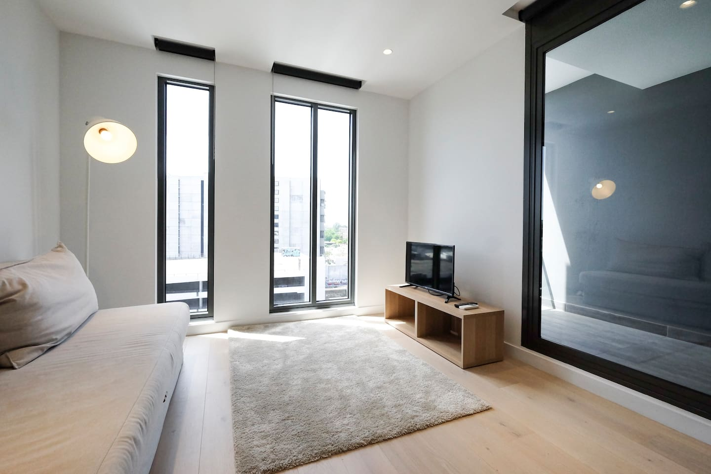 Spacious living room with abundant natural light and balcony.