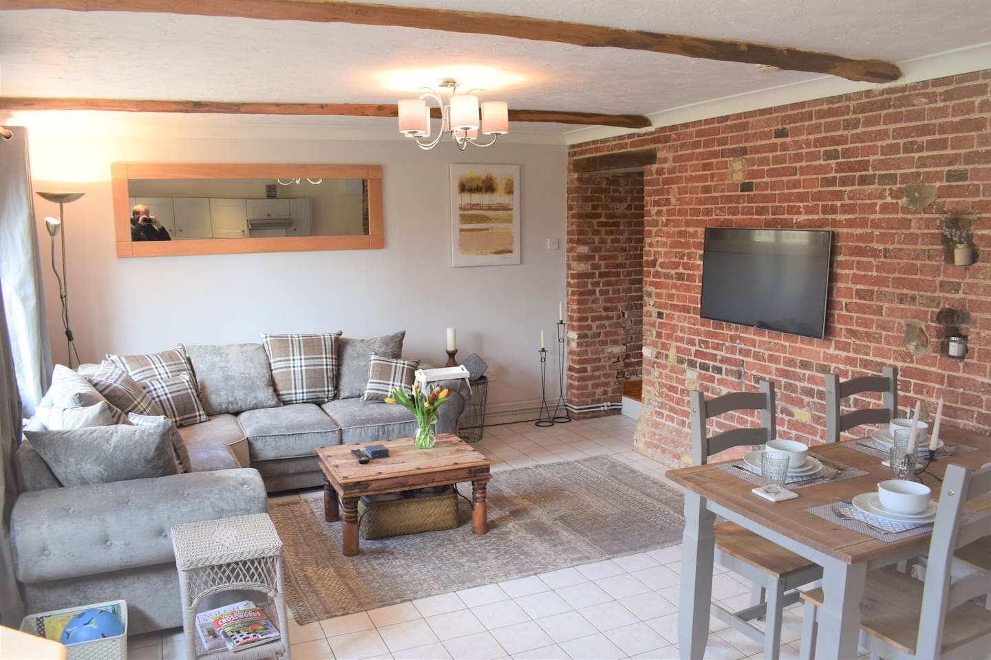 The stylish and contemporary living area of the Threshing Barn, with smart TV, comfy sofa, dining area and full kitchen.
