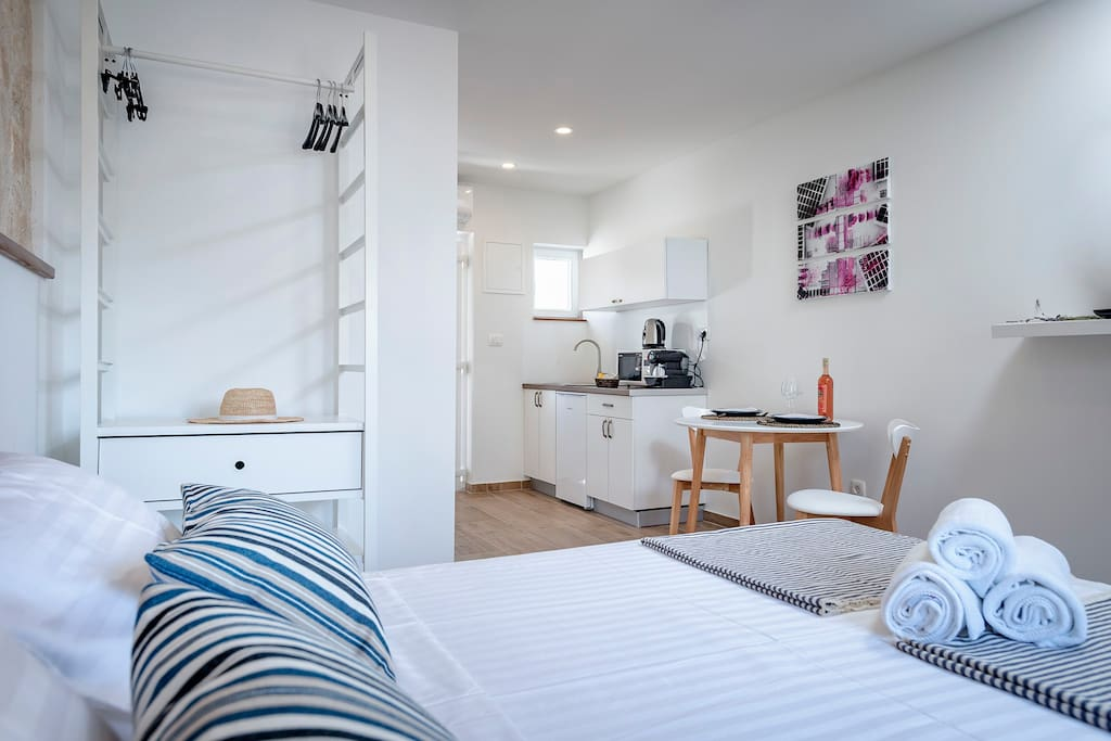 Double bed with the kitchen area and a dining table, newly renovated inside an old Hvar's stone house. The room has A/C and satellite smart TV