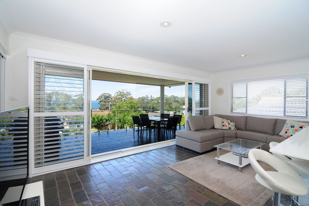 Living room and kitchen with sliding  plantation shutters, air con, large screen TV with Foxtel and  great view out across Jervis Bay