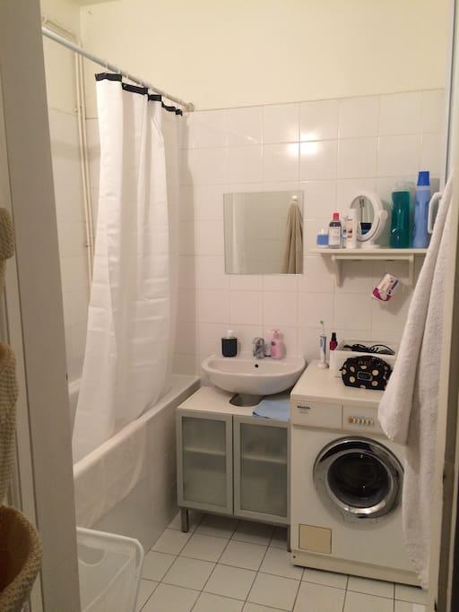 Salle de bain avec fenêtre, baignoire et machine à laver.