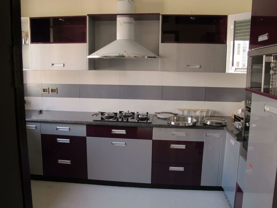 Fully equipped modular kitchen with fridge.