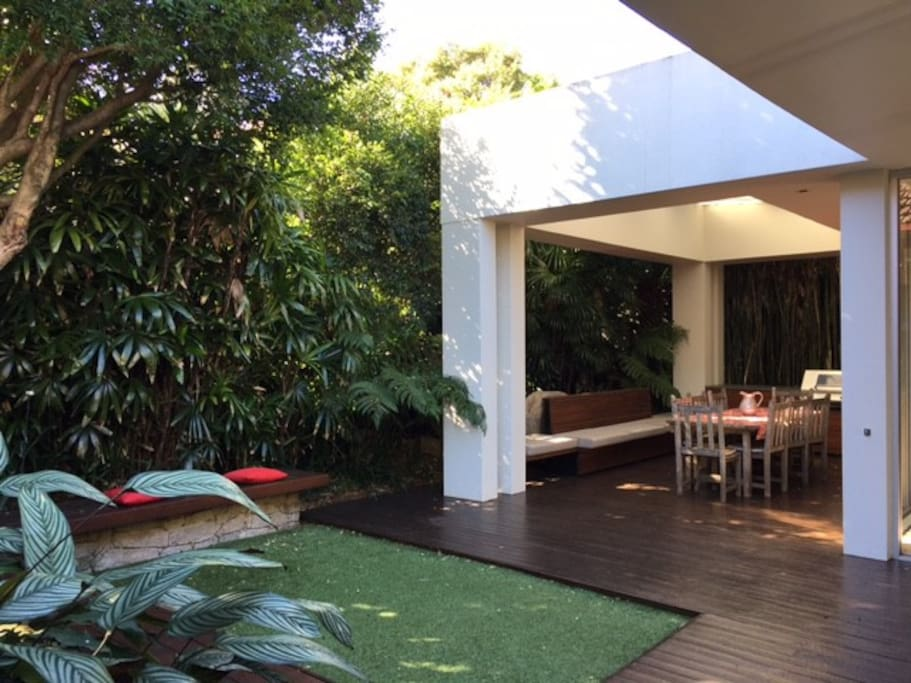 Lush tropical outdoor garden and entertaining area featuring covered BBQ dining area for all weather enjoyment