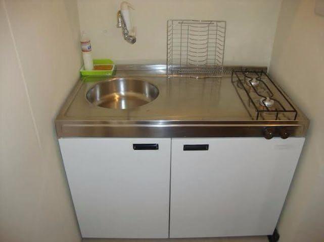 Armário da cozinha com pia, fogão e geladeira