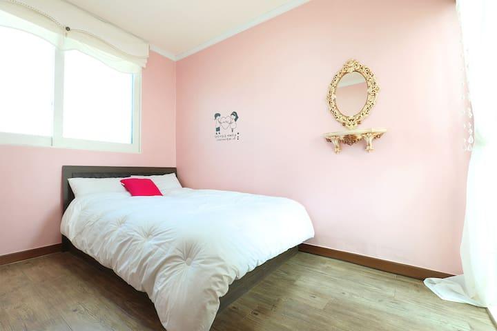 화이트 침구와 핑크빛 컬러가 소녀처럼 어여쁜 침대형 객실