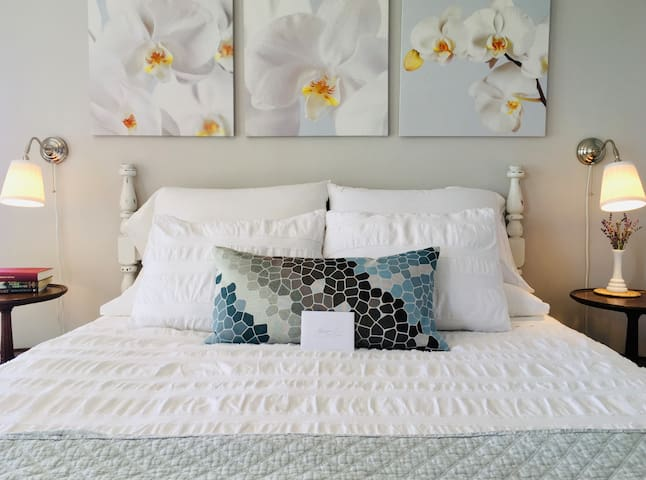 Comfortable queen size bed with spring/summer bedding.