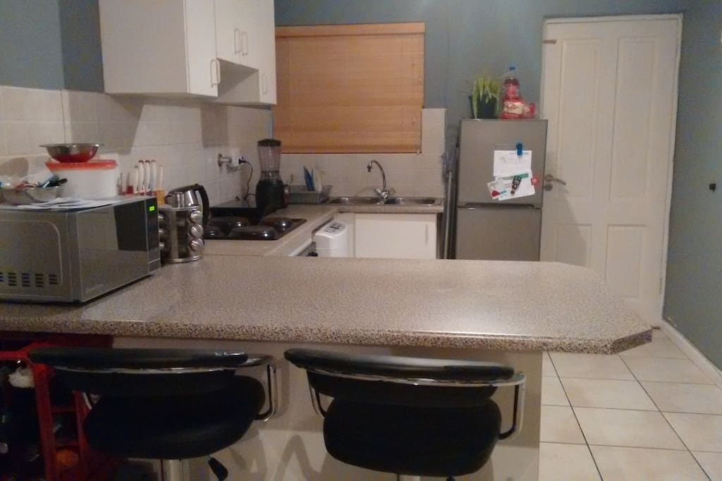 The kitchen with stools and a surface to work or eat on