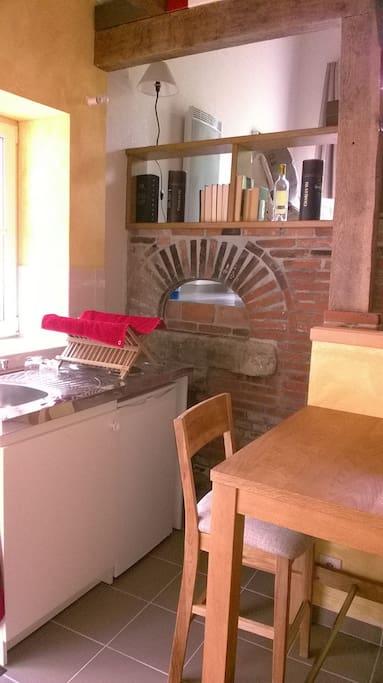 Petite cuisine équipée et vue sur l'ancien four à pain