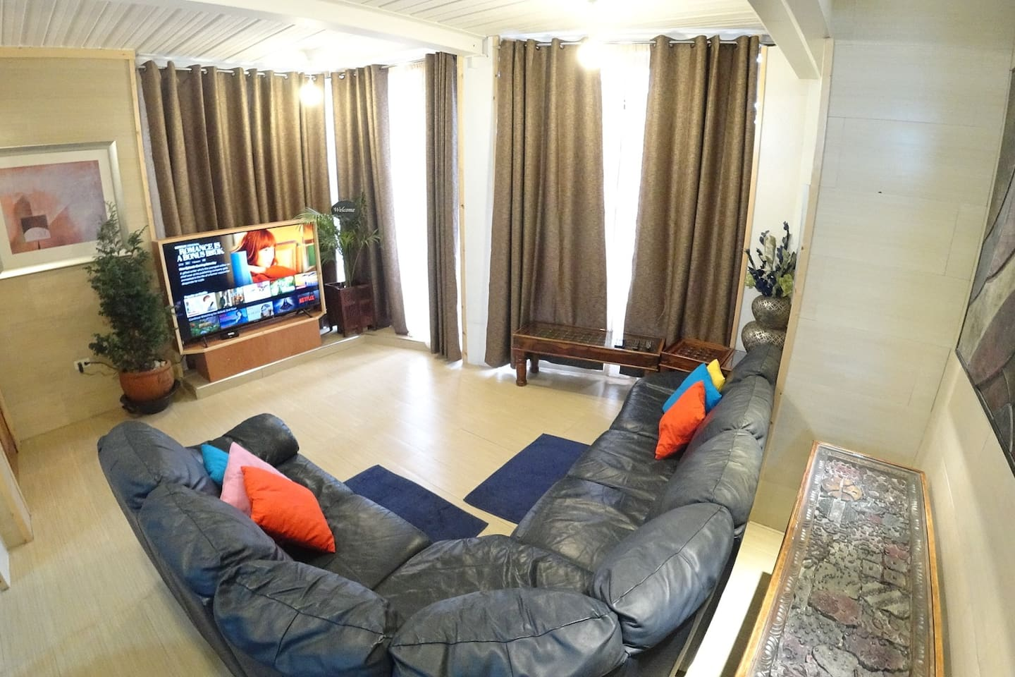 Living area with a large seating and a 65inch HD tv with Netflix