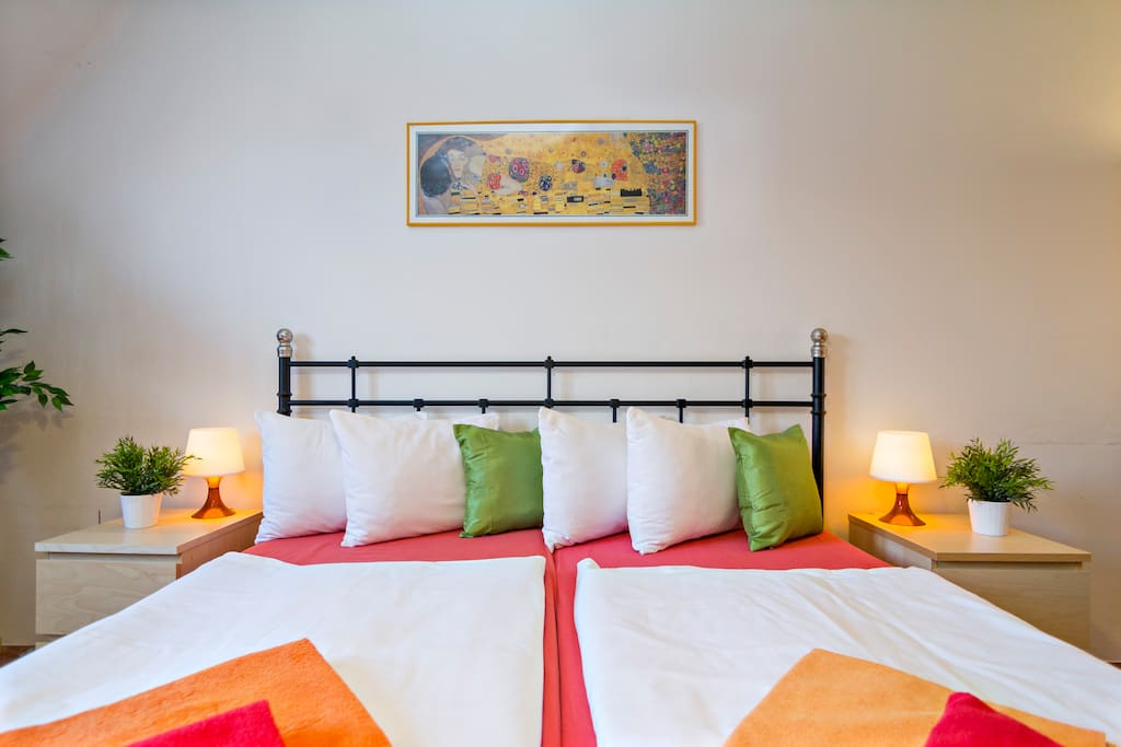 Spacious bedroom with double bed, comfy chair and dining area