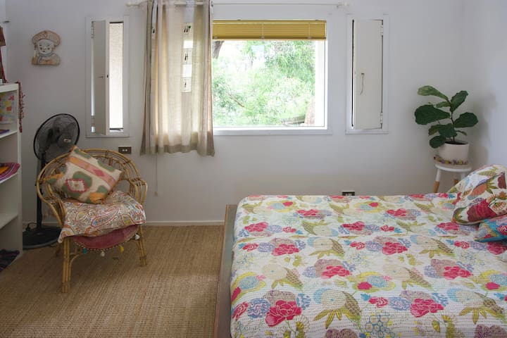 A spacious and bright bedroom with high ceiling and desk.