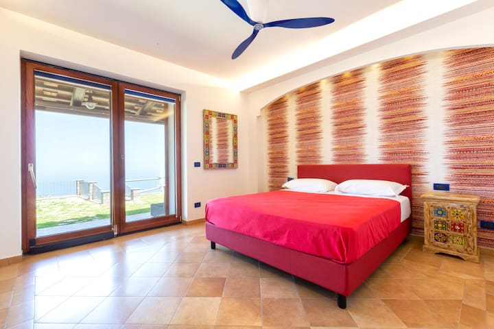 Bedroom 2 - Queen Bed, Fresh Linens, Cooling Fan, Free Wi-Fi 24hrs, Wardrobe and Storage Space, Mirror, Flat Screen TV, Large sliding doors where you can directly access the Garden Area and admire the Sea View