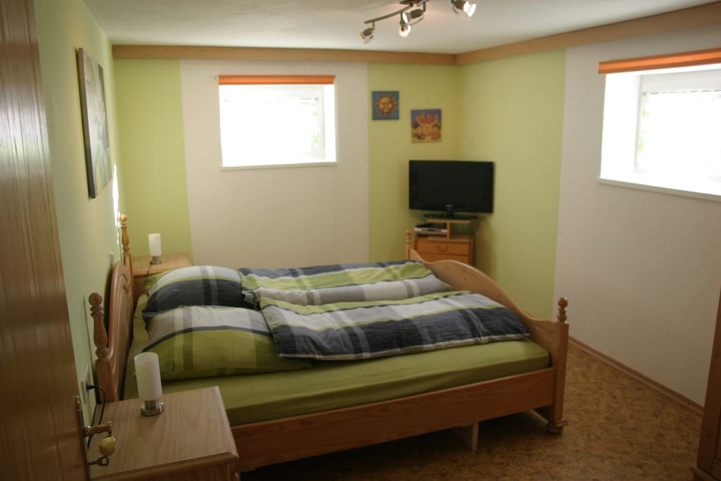 Schlafzimmer mit Doppelbett und Fernseehr