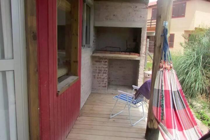 Deck lateral con parrillero techado junto a  la cocina y a su ventana.