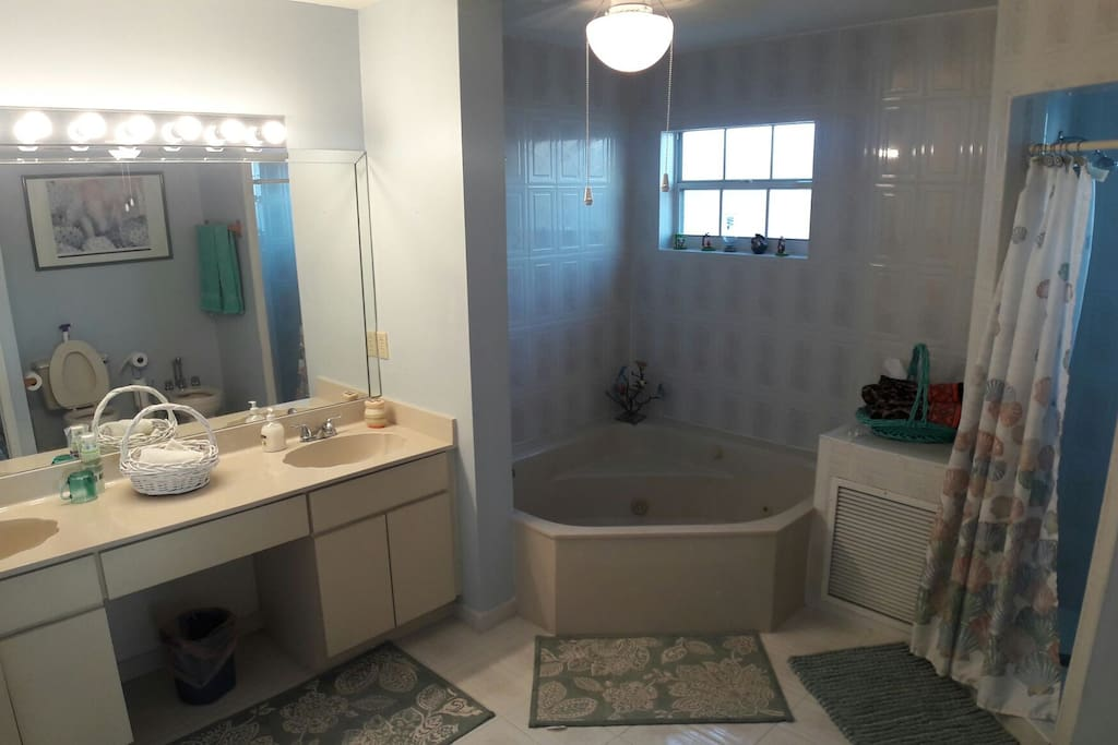This extra large bathroom features warm marble units and modern white sanitary ware. Huge shower and tub accompanied by two sinks, a large mirror and a window to brighten the room.