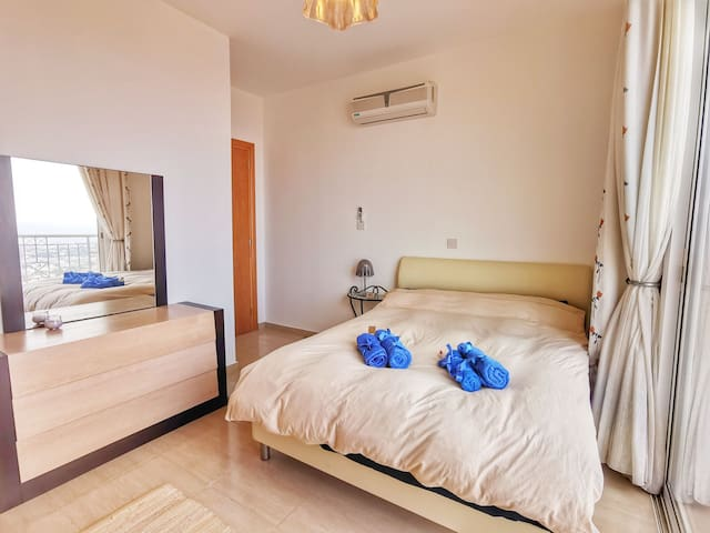 Sunny bedroom with double bed big wardrobe and entrance to the front balcony.