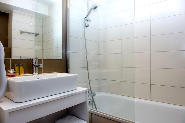 This bathroom features a shower and tub combination.