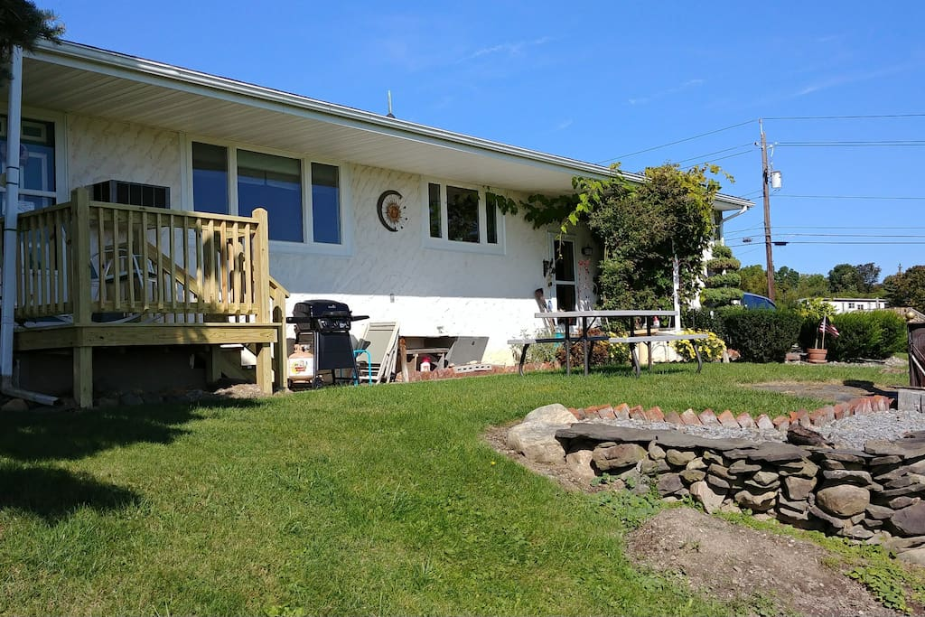 Front of house.  Sitting Deck, Gas Grill, Chairs, picnic table, outside water facet and wood stove for lake view enjoyment.
