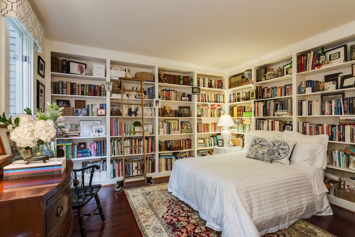 Private library suite with king bed surrounded by the most charming books