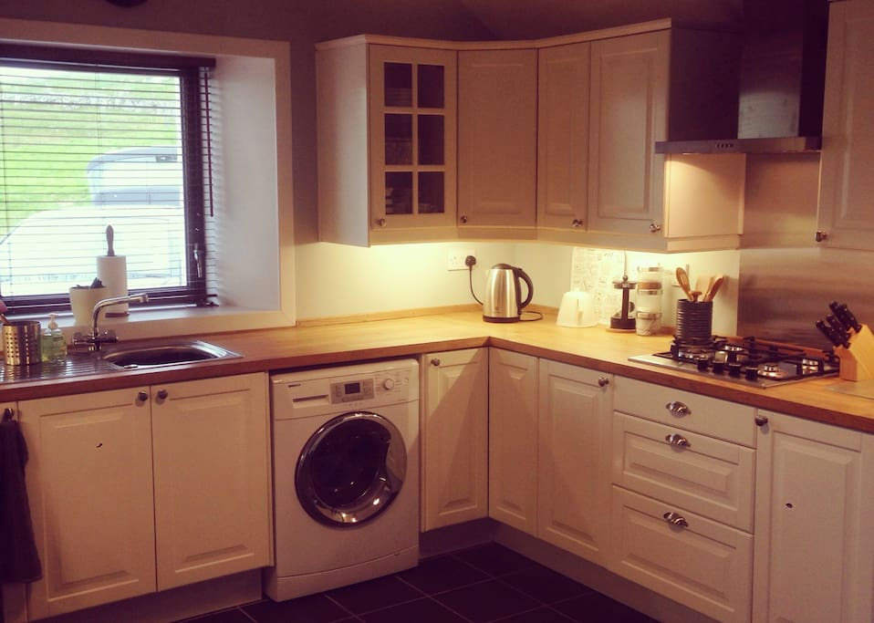 Kitchen with washing machine and gas hob.