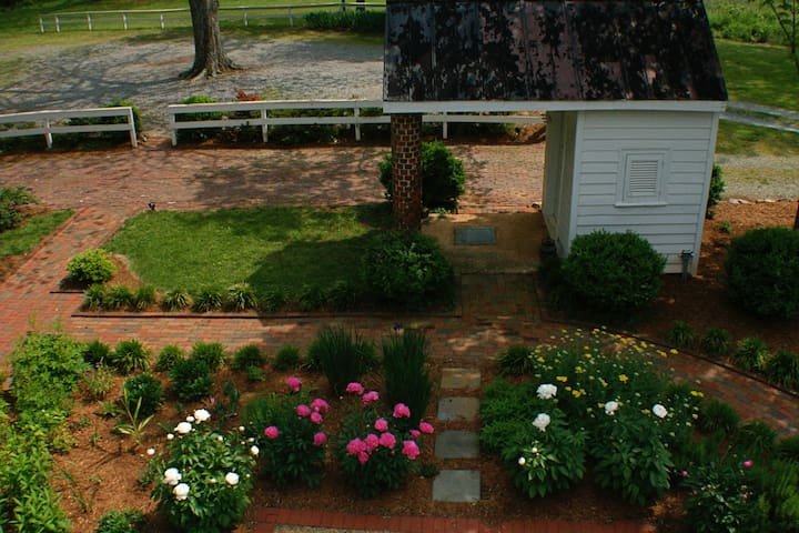 View from your window looking onto peonies in bloom in early May and original well house.